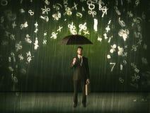 Hombre de negocios que se coloca con el paraguas y números 3d que llueven el concep Fotos de archivo