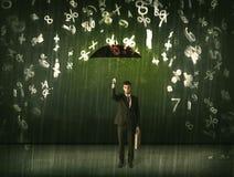 Hombre de negocios que se coloca con el paraguas y números 3d que llueven el concep Fotografía de archivo libre de regalías