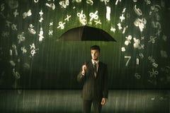 Hombre de negocios que se coloca con el paraguas y números 3d que llueven el concep Imagen de archivo