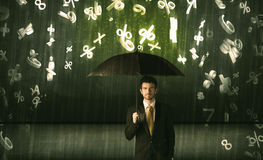 Hombre de negocios que se coloca con el paraguas y números 3d que llueven el concep Imagen de archivo libre de regalías
