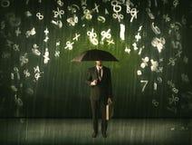 Hombre de negocios que se coloca con el paraguas y números 3d que llueven el concep Imagenes de archivo