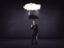Hombre de negocios que se coloca con el paraguas y poca nube de tormenta Imagen de archivo