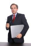 Hombre de negocios que se coloca con la computadora portátil foto de archivo
