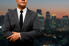 Hombre de negocios que se coloca con la luz de la ciudad en fondo Fotografía de archivo