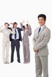 Hombre de negocios que se coloca con las personas que animan detrás de él Imagen de archivo