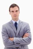 Hombre de negocios que se coloca con los brazos doblados Imagen de archivo libre de regalías