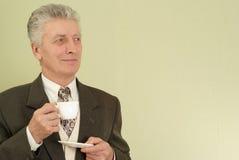 Hombre de negocios que se coloca con una taza Fotografía de archivo libre de regalías
