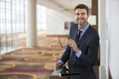 Hombre de negocios que se coloca confiado con el retrato de la sonrisa Imagen de archivo libre de regalías