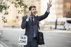 Hombre de negocios que se coloca de granizada de un taxi Fotos de archivo libres de regalías