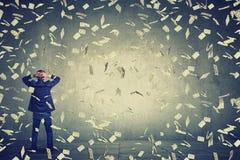 Hombre de negocios que se coloca delante de la pared debajo de los billetes de banco del dólar de la lluvia del dinero que caen a Fotografía de archivo libre de regalías