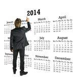 Hombre de negocios que se coloca delante de un calendario 2014 Imagenes de archivo
