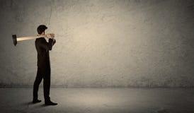 Hombre de negocios que se coloca delante de una pared sucia con un martillo Fotos de archivo libres de regalías