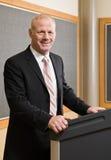 Hombre de negocios que se coloca detrás del podium Fotografía de archivo libre de regalías