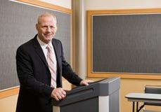 Hombre de negocios que se coloca detrás del podium Imagen de archivo libre de regalías