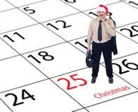 Hombre de negocios que se coloca en calendario de la Navidad Fotografía de archivo libre de regalías