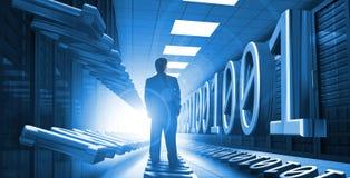 Hombre de negocios que se coloca en centro de datos con código binario Fotos de archivo libres de regalías