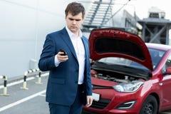 Hombre de negocios que se coloca en el coche quebrado y que usa el teléfono imágenes de archivo libres de regalías