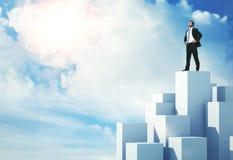 Hombre de negocios que se coloca en el cubo más alto Imagen de archivo