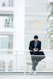 Hombre de negocios que se coloca en el edificio de oficinas Imágenes de archivo libres de regalías