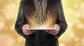 Hombre de negocios que se coloca en el fondo amarillo borroso que presenta nuevas tecnologías de la línea diagrama Imagenes de archivo