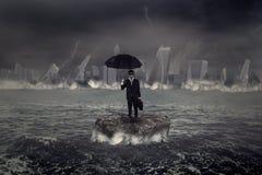 Hombre de negocios que se coloca en el mar con la tormenta de la crisis Fotos de archivo libres de regalías