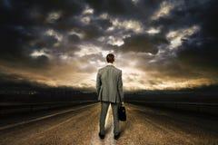 Hombre de negocios que se coloca en el medio del camino. Foto de archivo libre de regalías