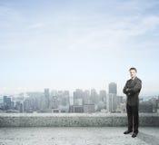 Hombre de negocios que se coloca en el tejado Fotografía de archivo