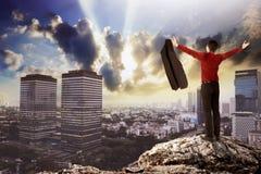 Hombre de negocios que se coloca en el top de la roca Imagen de archivo