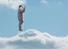 Hombre de negocios que se coloca en escalera sobre las nubes Fotos de archivo