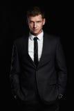 Hombre de negocios que se coloca en fondo negro Hombre joven hermoso en juego imagen de archivo libre de regalías