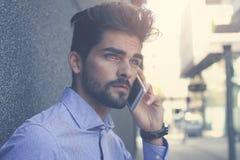 Hombre de negocios que se coloca en la calle y que habla en pho móvil fotografía de archivo libre de regalías