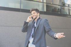 Hombre de negocios que se coloca en la calle y que tiene conversación o imagenes de archivo