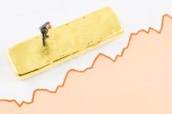 Hombre de negocios que se coloca en la carta del precio con la barra de oro Imagenes de archivo