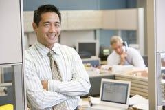 Hombre de negocios que se coloca en la sonrisa del cubículo foto de archivo