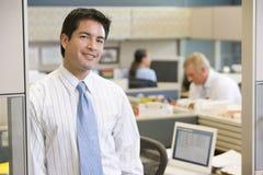 Hombre de negocios que se coloca en la sonrisa del cubículo imagenes de archivo