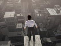 Hombre de negocios que se coloca en la tapa del rascacielos Imagen de archivo libre de regalías