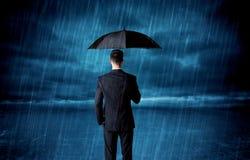 Hombre de negocios que se coloca en lluvia con un paraguas Foto de archivo libre de regalías