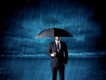Hombre de negocios que se coloca en lluvia con un paraguas Imagen de archivo