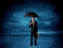 Hombre de negocios que se coloca en lluvia con un paraguas Fotos de archivo