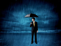 Hombre de negocios que se coloca en lluvia con un paraguas Fotos de archivo libres de regalías
