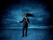 Hombre de negocios que se coloca en lluvia con un paraguas Imagenes de archivo