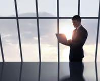 Hombre de negocios que se coloca en oficina Imagen de archivo