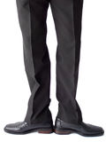 Hombre de negocios que se coloca en pantalones y zapatos negros Fotografía de archivo libre de regalías