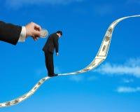 Hombre de negocios que se coloca en tendencia del dinero con la moneda que inserta en el CCB Foto de archivo