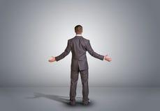 Hombre de negocios que se coloca en un cuarto gris vacío rear Fotografía de archivo libre de regalías