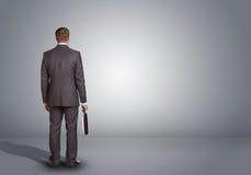Hombre de negocios que se coloca en un cuarto gris vacío rear Imágenes de archivo libres de regalías