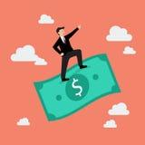 Hombre de negocios que se coloca en un dinero del vuelo Foto de archivo libre de regalías