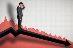 Hombre de negocios que se coloca en un gráfico y que mira abajo en los resultados Foto de archivo