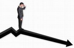 Hombre de negocios que se coloca en un gráfico y que mira abajo en los resultados Fotos de archivo
