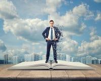 Hombre de negocios que se coloca en un libro abierto con las letras que cubren a su lado derecho Fotografía de archivo libre de regalías